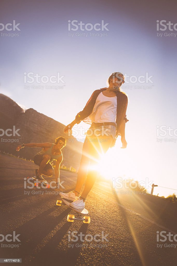 Couple skateboarding on road in sunset stock photo