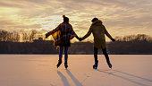 Couple skating on frozen lake on sunset