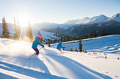 Couple skiing on a sunny powder day