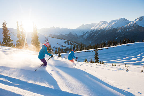 Couple skiing on a sunny powder day stock photo