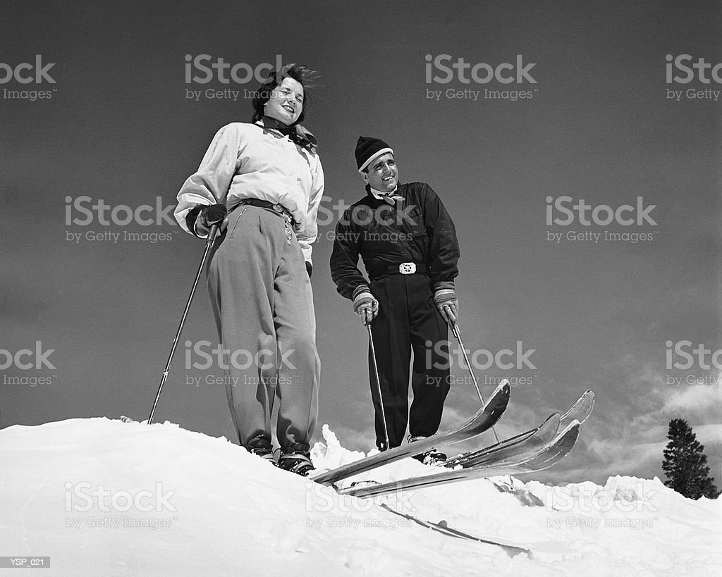 Couple skiing, stopped at top of hill royalty-free stock photo