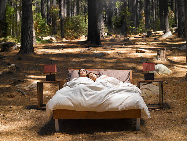 A couple sleeping in a bed outdoors in the woods stock photo