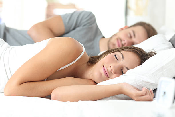 Couple sleeping in a comfortable bed stock photo