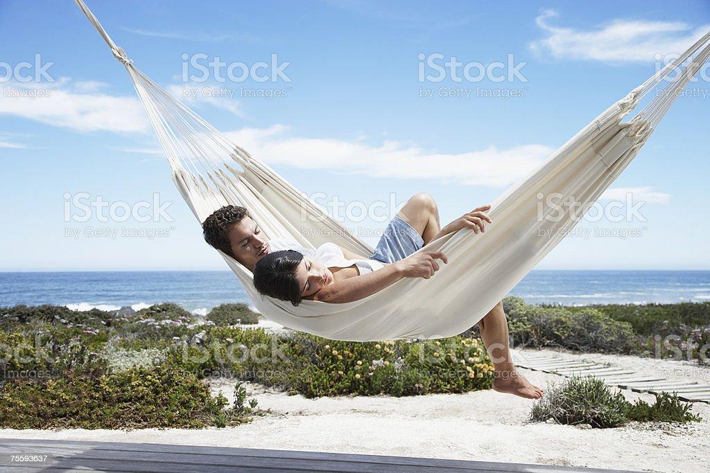 A couple sleeping in a hammock stock photo