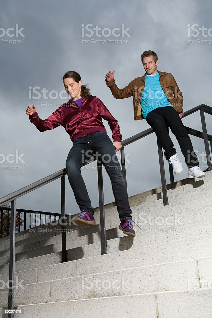 Couple sliding down railings royalty-free stock photo