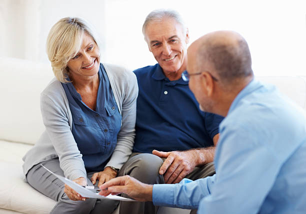 couple smiling and listening to financial planner - financial advisor with clients stock photos and pictures