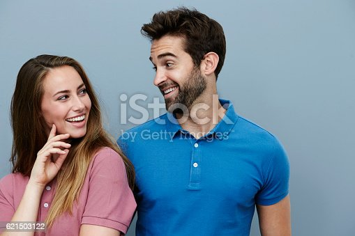 istock Couple smiling at each other in polo shirts 621503122