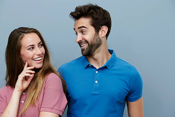 Couple smiling at each other in polo shirts stock photo