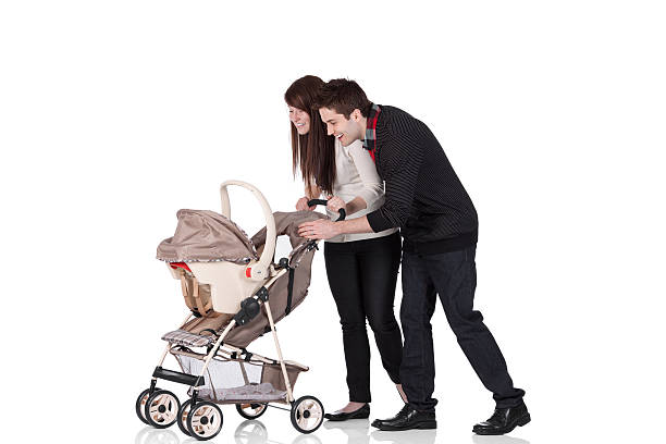 Couple smiling at their baby in a pram stock photo
