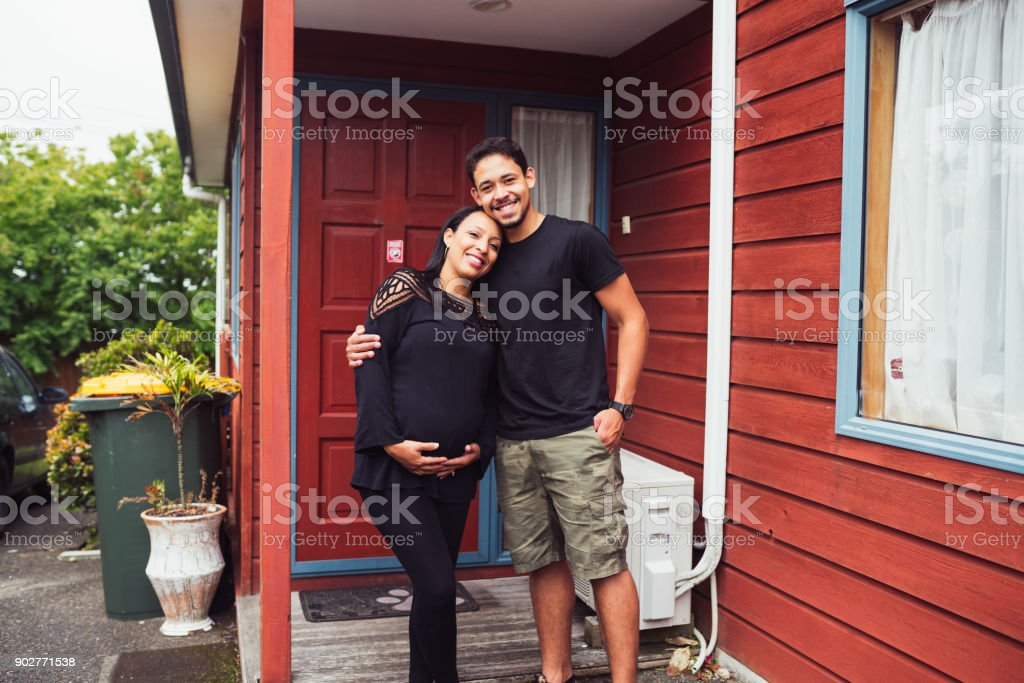 Couple smiling in front of their house. stock photo