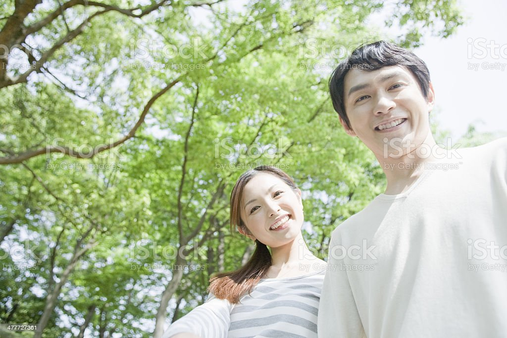 Couple smiling in greenery stock photo