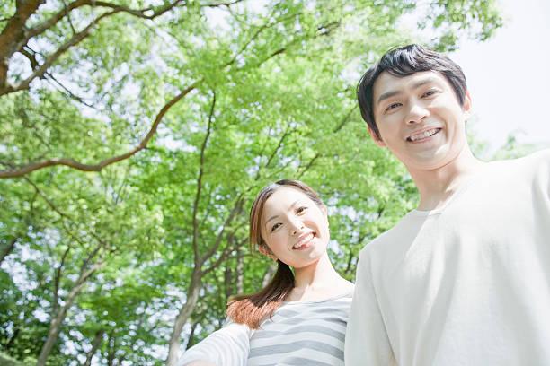 couple smiling in greenery - mid volwassen koppel stockfoto's en -beelden
