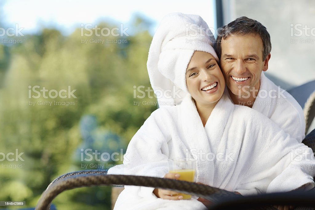Couple smiling sitting outdoors wrapped in towels royalty-free stock photo