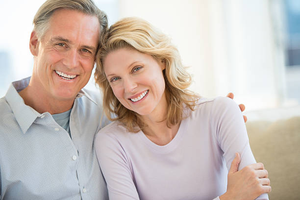Couple Smiling Together At Home Portrait of mature couple smiling together at home 40 44 years stock pictures, royalty-free photos & images