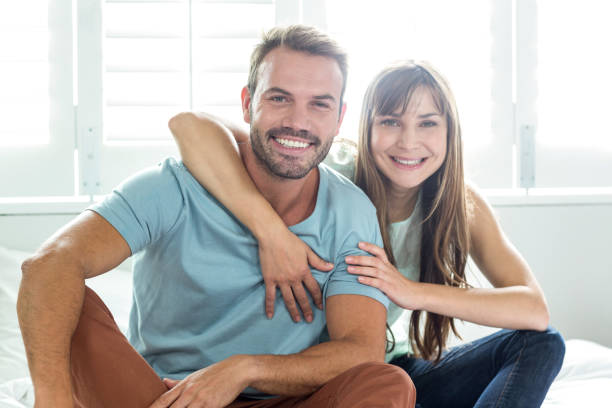 Couple smiling while relaxing on bed Portrait of couple smiling while relaxing on bed at home 30 39 years stock pictures, royalty-free photos & images