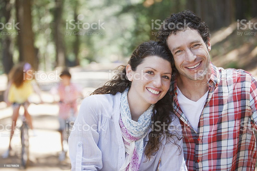 Couple smiling with children on bicycles in background royalty-free stock photo