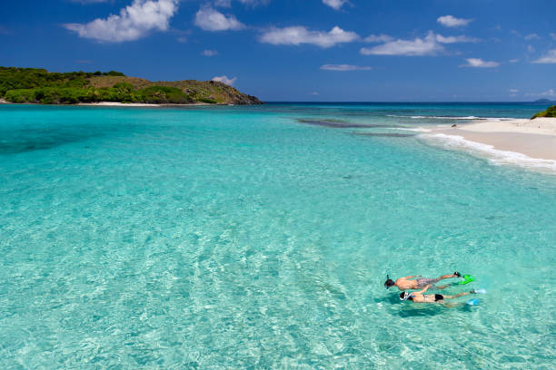 Couple snorkeling at a tropical deserted island in the caribbean