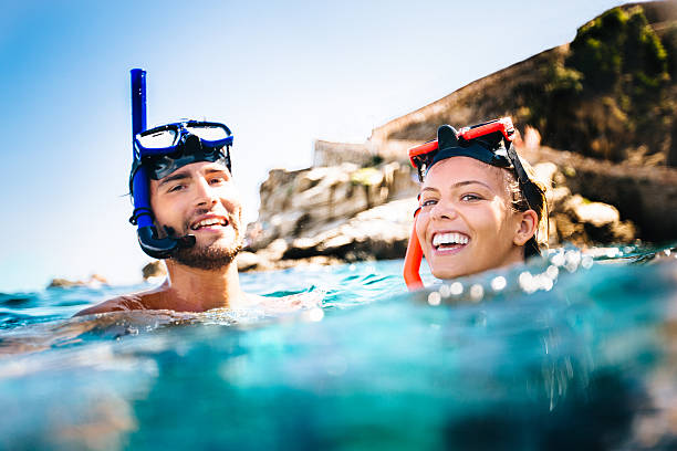 Couple Snorkeling Couple snorkeling on holiday snorkel stock pictures, royalty-free photos & images