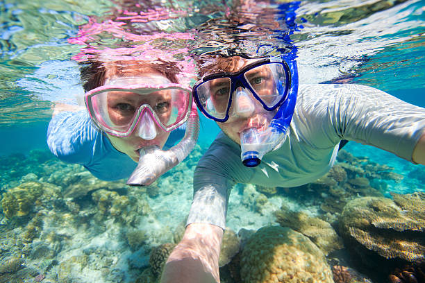 A couple snorkeling together on shallow water stock photo