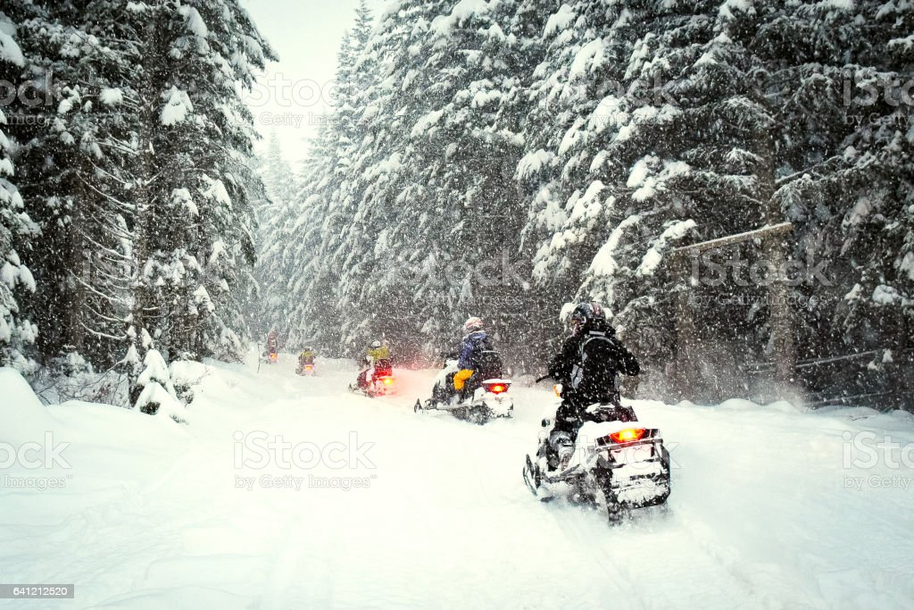 Couple snow mobile in snow storm stock photo