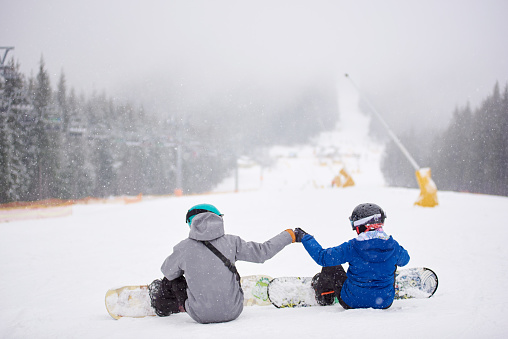 Couple snowboarders sitting on snow on ski run wooded slope at ski resort in snowfall with their boards on. Back view