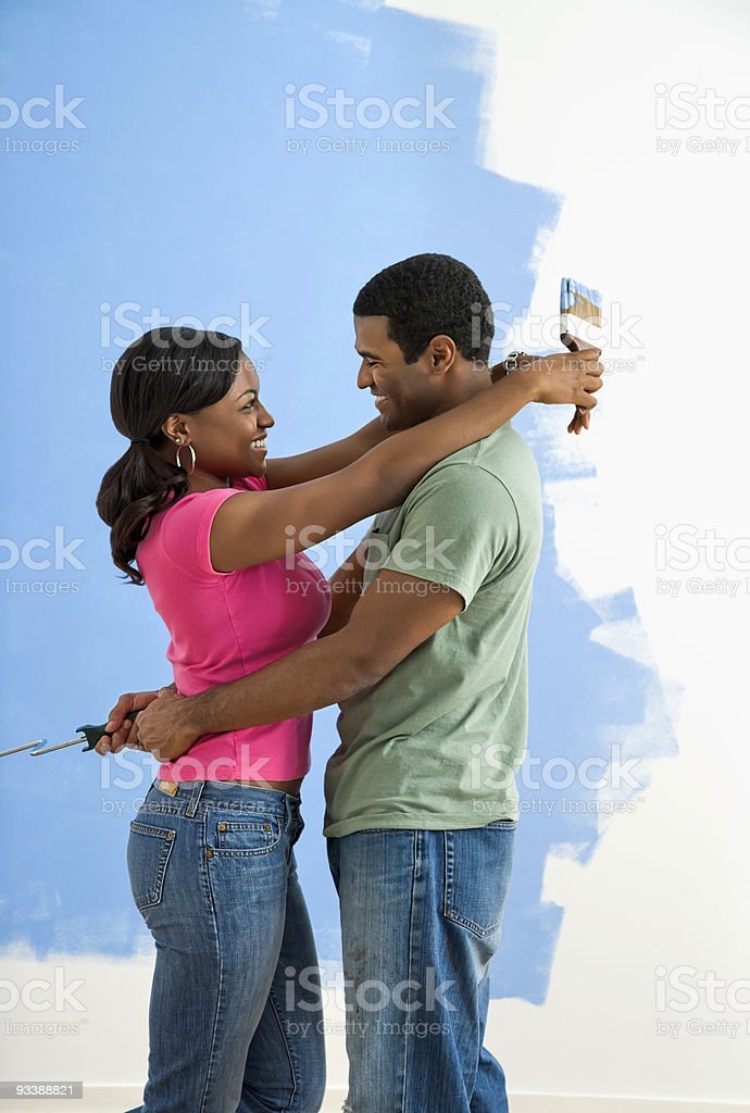 Couple snuggling next to half-painted wall. royalty-free stock photo
