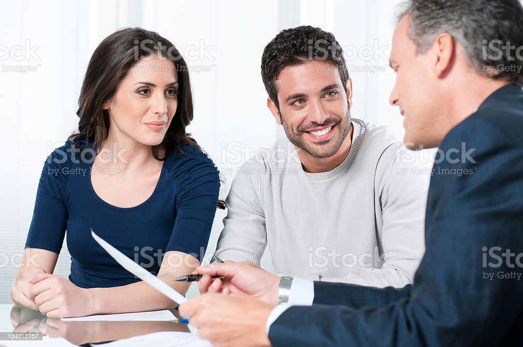 Couple speaking with an investment consultant stock photo
