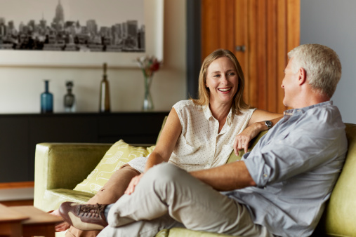 Happy mature couple spending leisure time in living room