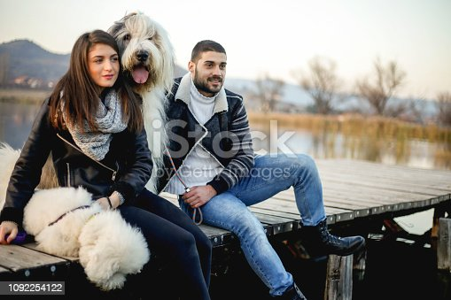 Couple spending time together on the pier with their dogs