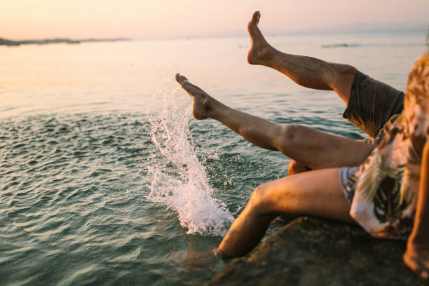 Couple splashing water with barefoot in the sea stock photo