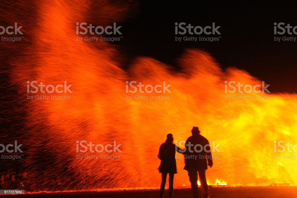 Couple stand in-front of a large bonfire at night