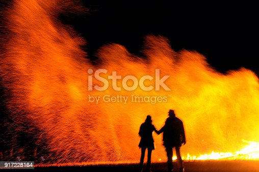 istock Couple stand in-front of a large bonfire at night 917228164
