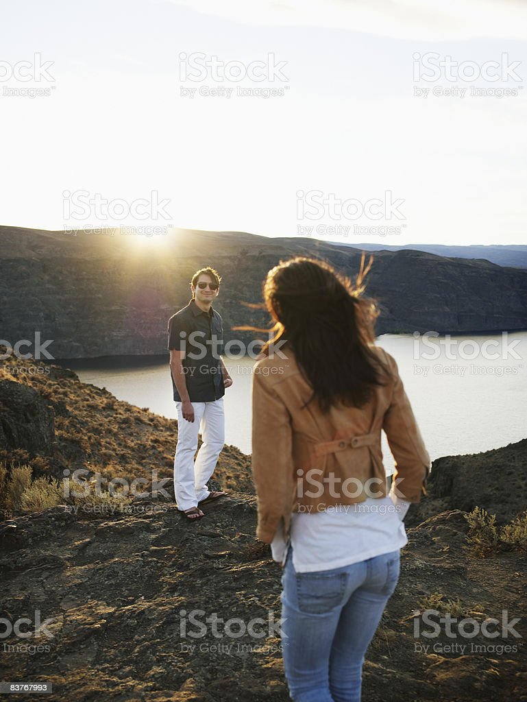 Couple standing above river gorge watching sunset photo libre de droits