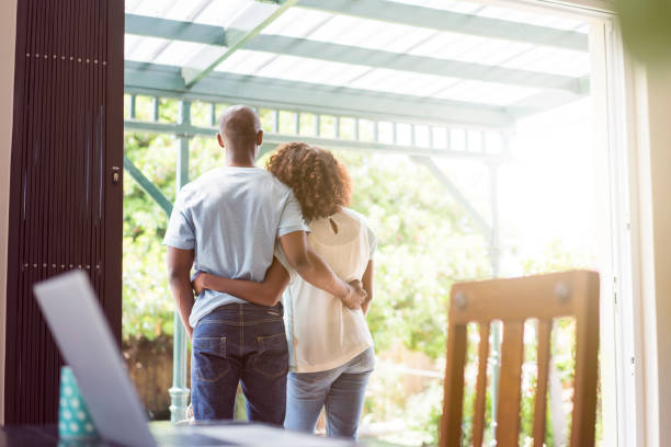 Couple standing arms around at entrance stock photo