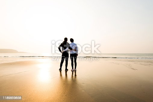 Couple standing at beach with arm around.