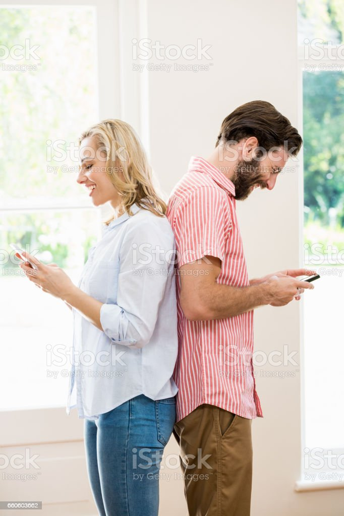 Couple standing back to back and text messing on mobile phone royalty-free stock photo