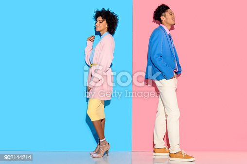 istock couple standing back to back on pink and blue background 902144214