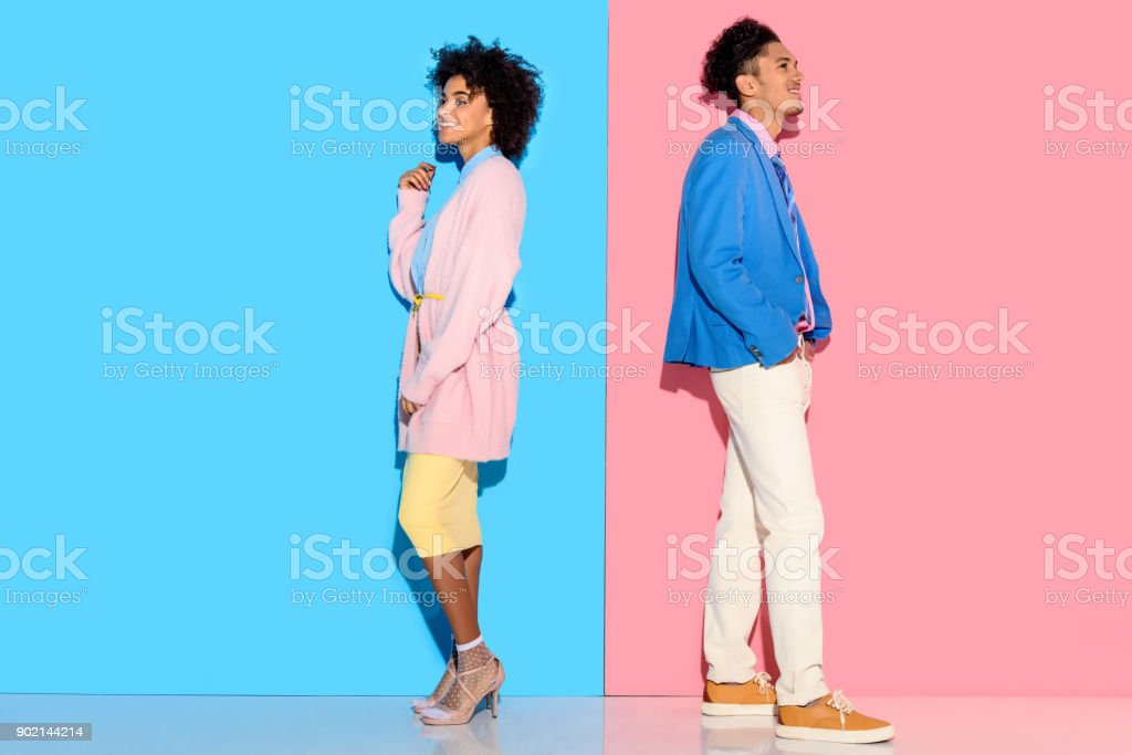 couple standing back to back on pink and blue background stock photo