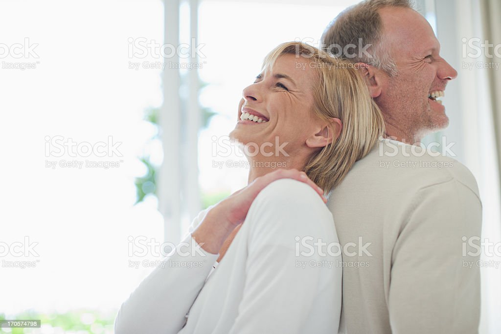 Couple standing back to back stock photo