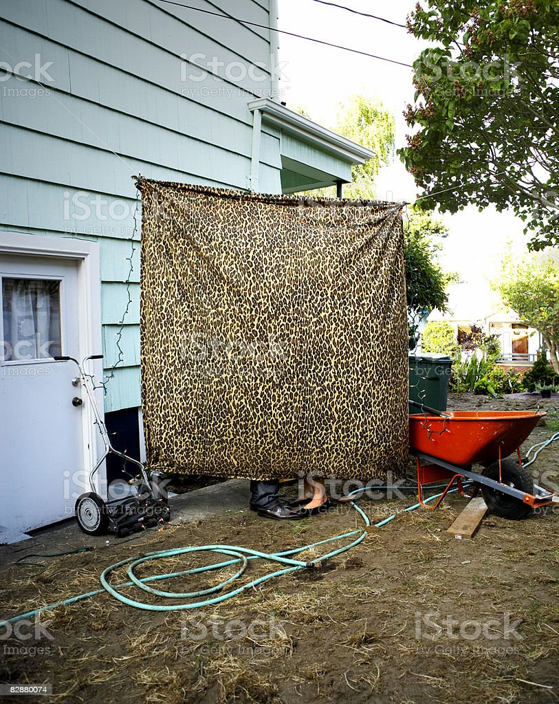 Couple standing behind curtain in backyard royaltyfri bildbanksbilder