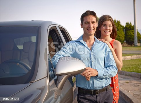 Couple standing beside car