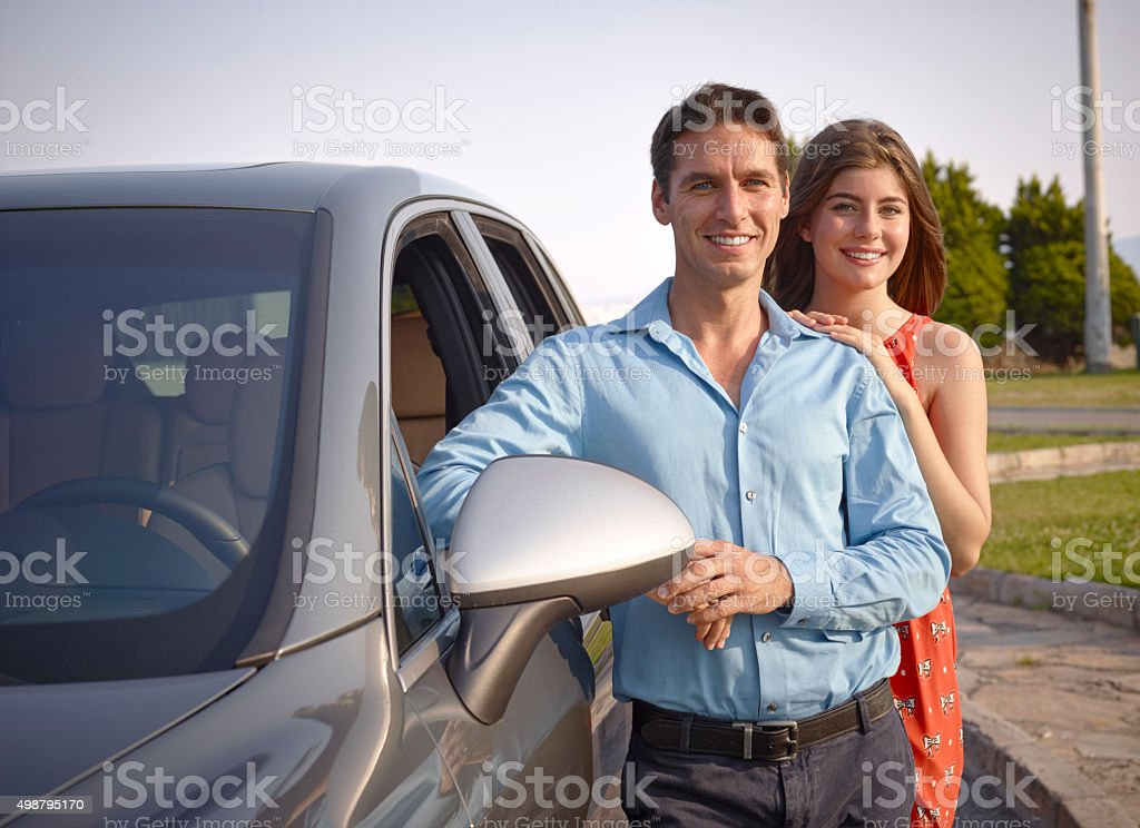 Couple standing beside car stock photo