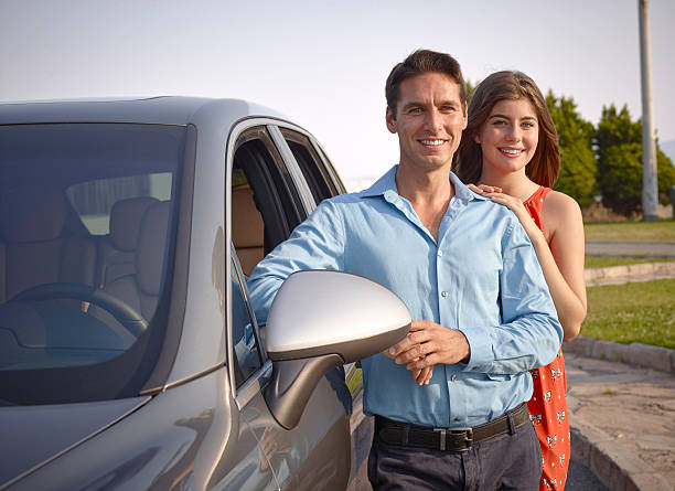 Couple standing beside car Couple standing beside car alongside stock pictures, royalty-free photos & images