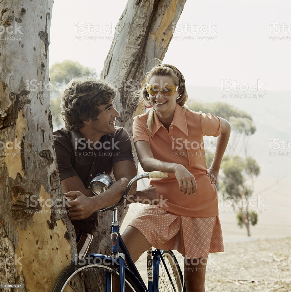 Couple standing beside tree with bicycle stock photo