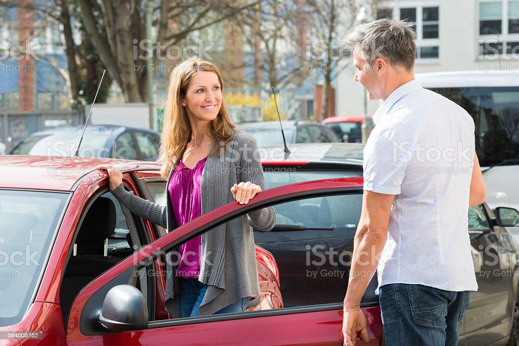 Couple Standing By New Car Door stock photo