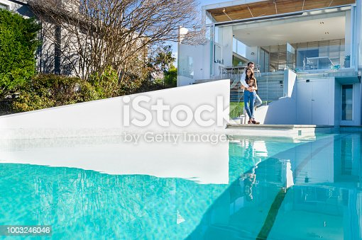 Couple standing by the swimming pool of luxury new house. There is a swimming pool in the foreground. They are embracing and romantic. Could be a vacation, or they have just bought a new home. Looking at camera
