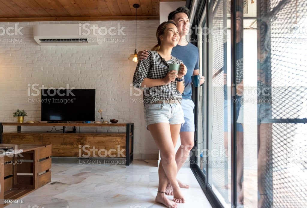 Couple standing by the window stock photo