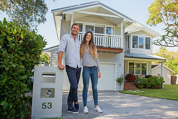 couple standing by their mailbox in front of new home stock photo