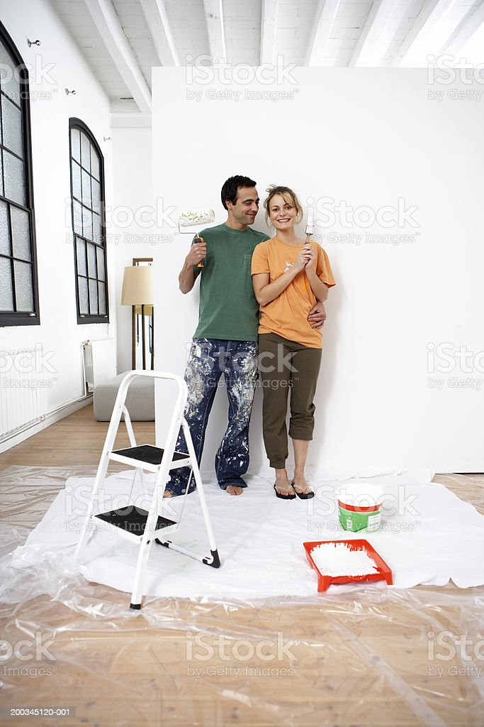 Couple standing by wall holding paint roller and brush royalty-free stock photo