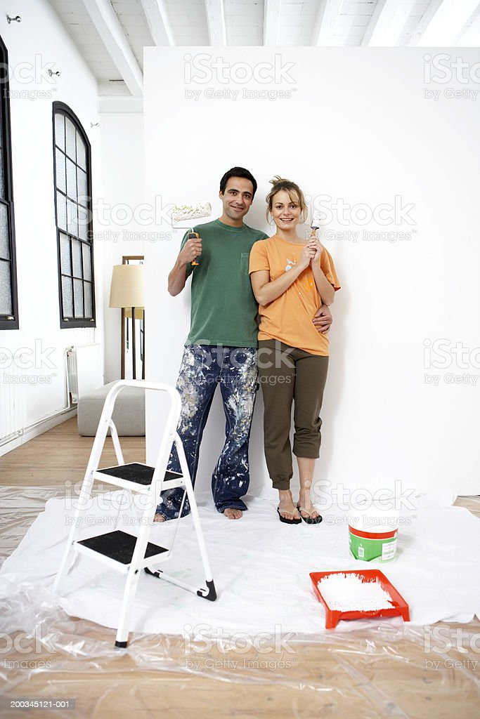 Couple standing by wall holding paint roller and brush, portrait royalty-free stock photo